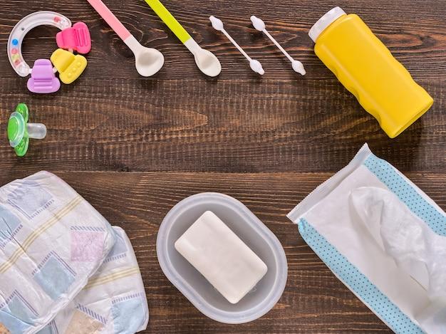 Japanse luiers, vochtige doekjes, zeep, babypoeder, titer, wattenstaafjes, lepels, fopspeen en eendje op donkerbruine houten achtergrond met kopie ruimte