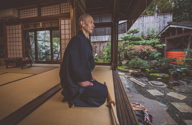 Japanse man mediteren in zijn tuin