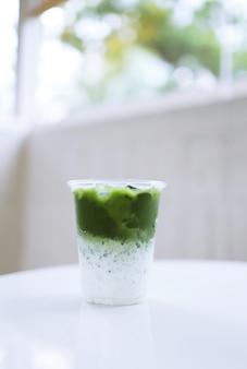 Japanse matcha groene thee latte in glazen beker.
