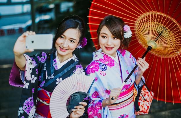 Japanse meisjes die kimono's traditionele kleding, levensstijlmomenten dragen