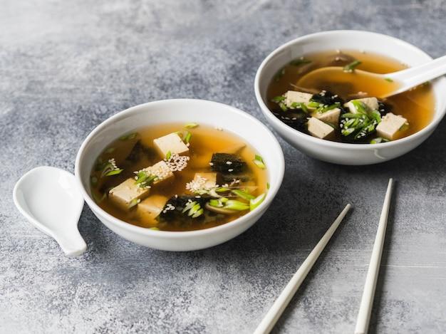 Japanse miso soep met oesterzwammen in witte kommen met een lepel en witte eetstokjes op een grijze achtergrond. kopie ruimte