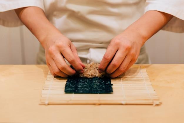 Japanse omakase chef-kokhand die een tonijn nori handroll netjes rollen met zijn hand op een houten aanrecht.