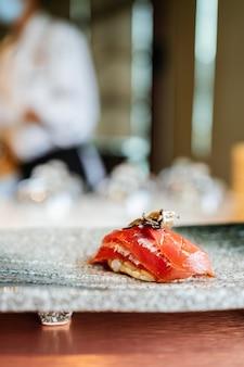 Japanse omakase-maaltijd. aging raw akami tuna sushi wordt toegevoegd met gesneden truffel die met de hand op een stenen bord wordt geserveerd.