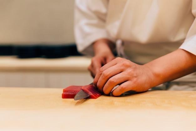 Japanse omakasechef snijdt blauwvintonijn (otoro in het japans) netjes met een mes.