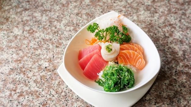 Japanse rijst met mix sashimi don in een witte kom.