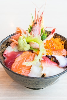 Japanse rijstkom met sashimizeevruchten op bovenkant