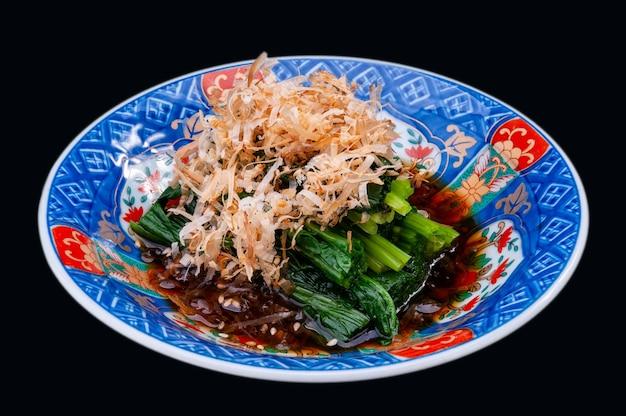 Japanse stijl gekookte spinazie in shoyusaus met zwarte achtergrond.