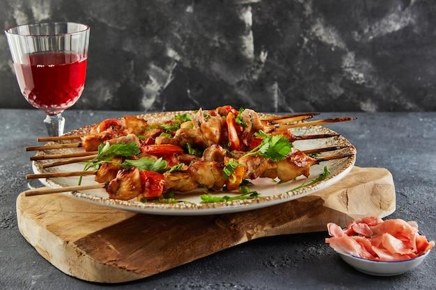 Japanse stijl yakitori shashlik op een houten bord met een glas rode wijn en gember. kopieer ruimte voor tekst.