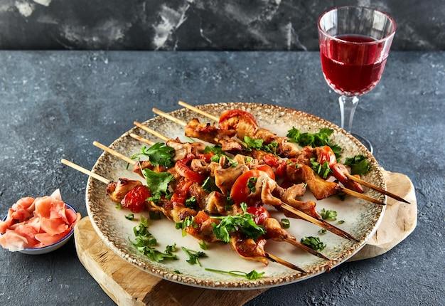 Japanse stijl yakitori shashlik op een houten bord met een glas rode wijn en gember