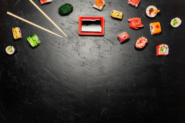 Japanse sushi en eetstokjes op zwarte achtergrond. sushi rollen, nigiri, maki