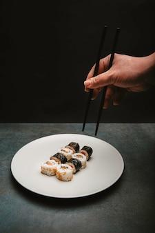 Japanse sushi rijst roll zalm en kaas gepresenteerd op een witte plaat met de actie van een handgeplukte sushi