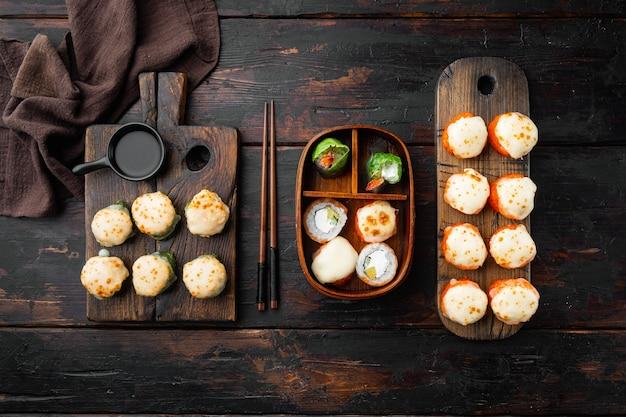 Japanse sushi rolt genaamd baked ebi met wasabi en zalm vis set, op oude donkere houten tafel