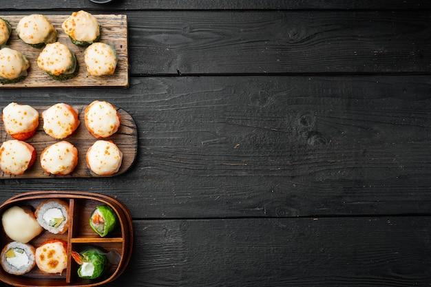Japanse sushi rolt genaamd baked ebi met wasabi en zalm vis set, op zwarte houten tafel