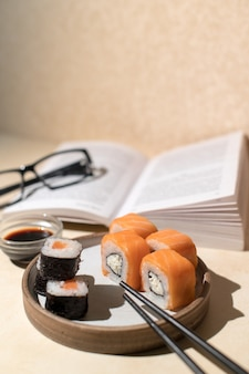 Japanse sushibroodjes die op lichte plaat, beige achtergrond worden gediend. boek en lunch. thuis ontspannen concept