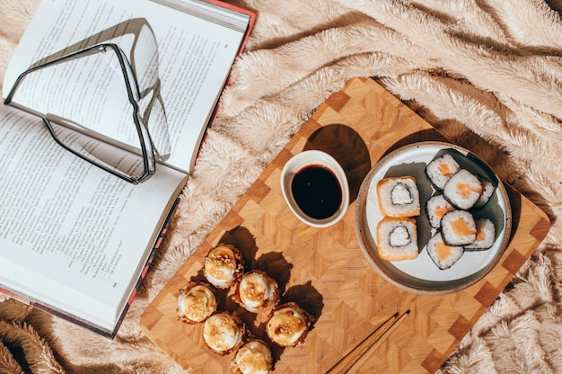 Japanse sushibroodjes die op lichte raad, beige achtergrond worden gediend. sushirolletjes philadelphia, warm gebakken broodje met room, maki, eetstokjes en sojasaus