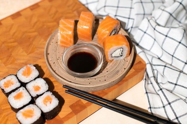 Japanse sushibroodjes die op plaat op houten achtergrond worden gediend. sushi rolt philadelphia, maki, eetstokjes en sojasaus
