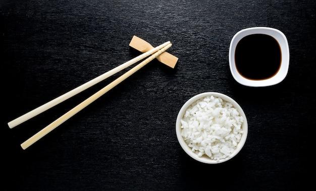 Japanse sushieetstokjes over sojasauskom, rijst op zwarte achtergrond
