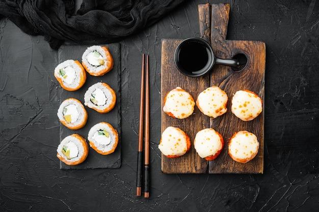Japanse sushirolletjes genaamd baked ebi met wasabi en zalmvisstel, op zwarte steen