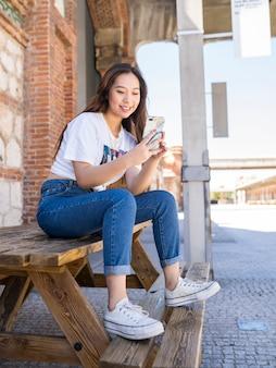 Japanse vrouw aan het chatten op haar telefoon zittend op een bankje