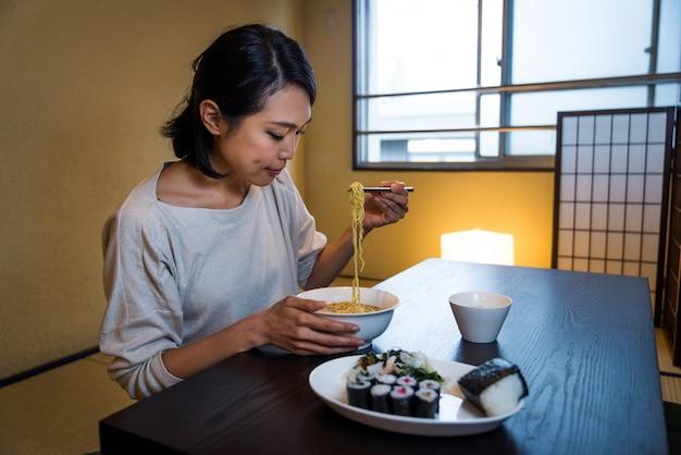 Japanse vrouw die in een traditionele flat eet