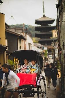 Japanse vrouw, gekleed in kimono oude traditionele kleding, zittend in riksja op yasaka street, yasaka shrine een van de meest populaire reisbestemmingen in kyoto