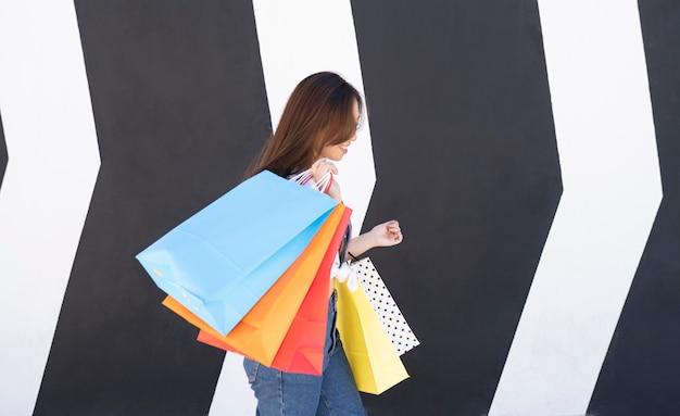 Japanse vrouw houdt kleurrijke boodschappentassen in de ene hand terwijl ze mobiel aan het chatten is