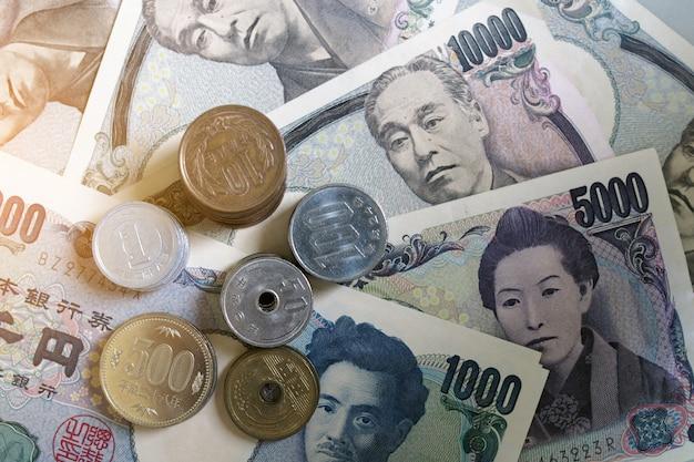Japanse yen-bankbiljetten en japanse yenmuntstukken voor de achtergrond van het geldconcept