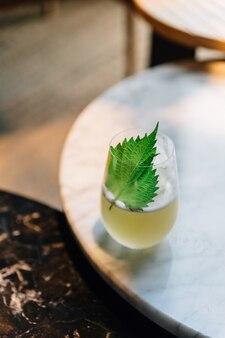 Japanse yuzu-cocktail met shiso-blaadjes (groene perilla) in glas op marmeren tafel.
