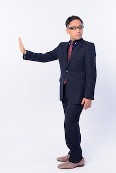 Japanse zakenman in pak die oogglazen draagt die op wit wordt geïsoleerd