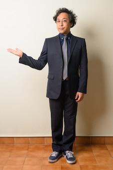 Japanse zakenman in pak met krullend haar binnenshuis