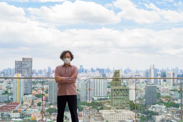 Japanse zakenman met krullend haar draagt masker ter bescherming tegen uitbraak van coronavirus tegen uitzicht op de stad