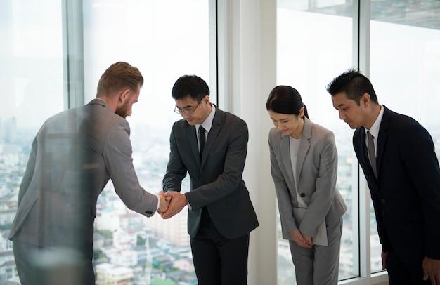 Japanse zakenmanmensen die een handdruk met een collega hebben