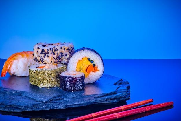 Japanse zeevruchtensushi die op een steen op blauw worden geplaatst