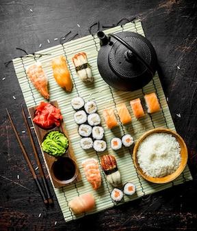 Japanse zeevruchtensushi op een servet met gekookte rijst en groene thee. op rustieke ondergrond
