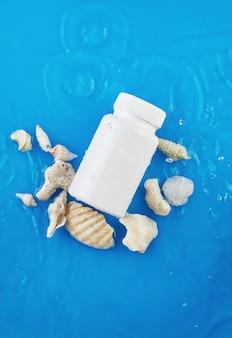 Jar mockup op blauwe achtergrond in water met golven en schelpen.