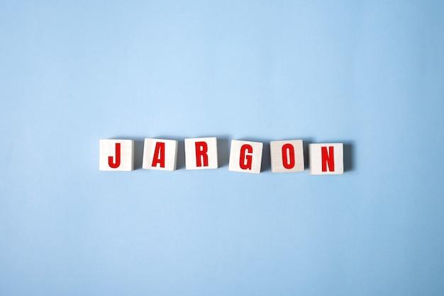 Jargon - woord uit houten blokken, speciale woorden en zinnen jargon concept, bovenaanzicht op blauwe achtergrond.