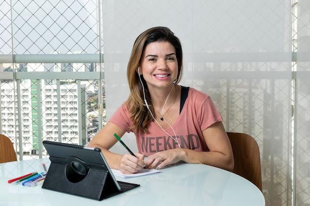 39-jarige vrouw op het balkon van het appartement aan het werk, bij de barbecue en zittend op de bank.