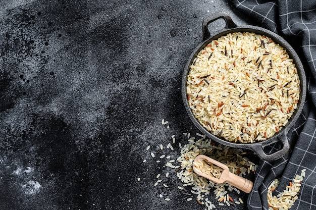 Jasmijn, bruine, rode en zwarte rijst. gemengde rijst en riceberry. zwarte achtergrond. bovenaanzicht. kopieer ruimte