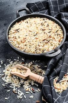 Jasmijn, bruine, rode en zwarte rijst. gemengde rijst en riceberry. zwarte achtergrond. bovenaanzicht