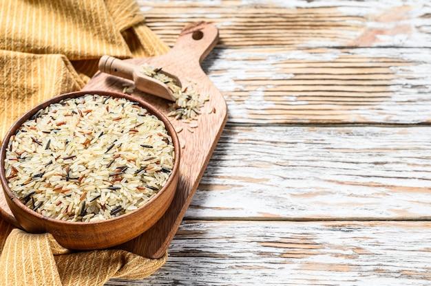 Jasmijn, bruine, rode en zwarte rijst in een kom. gemengde rijst en riceberry. witte achtergrond. bovenaanzicht. kopieer ruimte