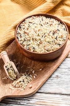 Jasmijn, bruine, rode en zwarte rijst in een kom. gemengde rijst en riceberry. witte achtergrond. bovenaanzicht.