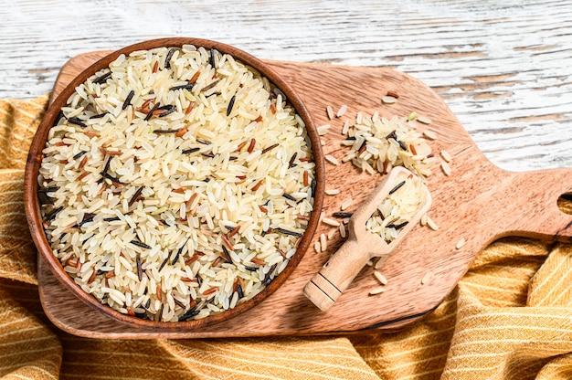 Jasmijn, bruine, rode en zwarte rijst in een kom. gemengde rijst en riceberry. witte achtergrond. bovenaanzicht