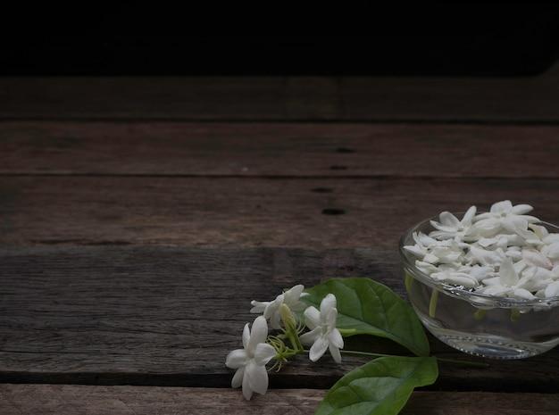 Jasmijn die in duidelijk glas op houten achtergrond drijft.