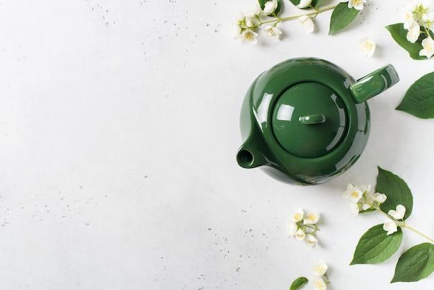 Jasmijn thee met theepot, bloemen en bladeren op witte achtergrond, kopie ruimte, bovenaanzicht