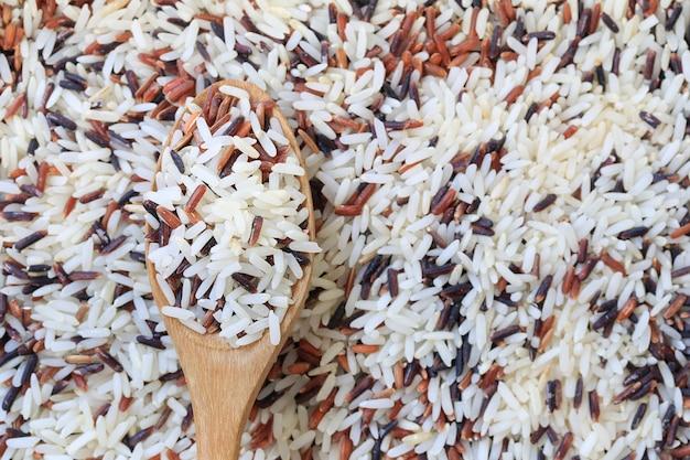 Jasmijnrijst in houten lepel op ongepelde rijstachtergrond.