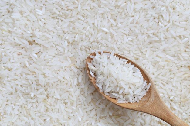 Jasmijnrijst in houten lepel op witte rijstachtergrond.