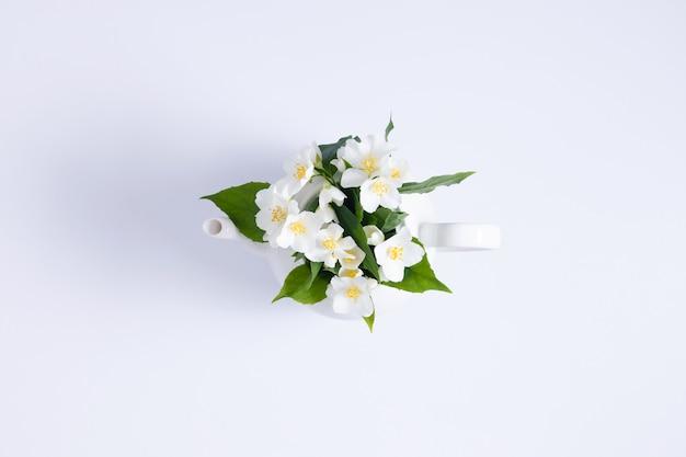 Jasmijnthee en bloementheepot met jasmijnbloemen op witte achtergrond flat lay