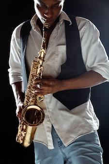 Jazzmuzikant die de saxofoon in de studio op een zwarte muur speelt