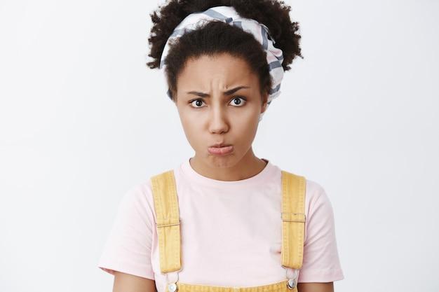 Je beloofde tijd met me door te brengen. portret van boos en beledigd triest afro-amerikaanse vrouw in hoofdband en gele tuinbroek, lippen tuit, fronsen en mokkend van belediging over grijze muur