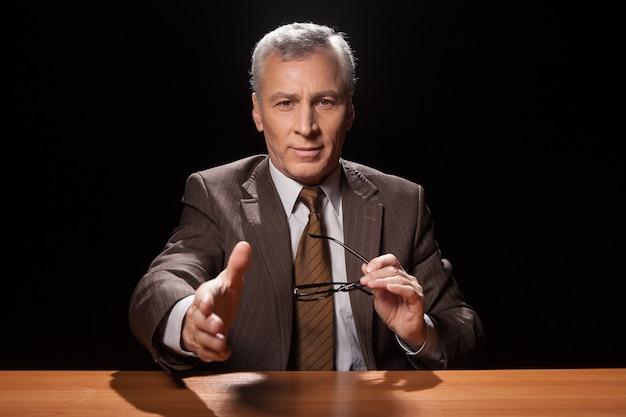 Je bent aangenomen! vrolijke senior man in formalwear zit op zijn werkplek en strekt zijn hand uit om te schudden terwijl hij geïsoleerd is op zwarte achtergrond